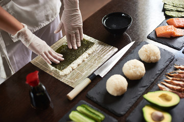 Close-up view of chef's hands preparing rolling sushi with ingredients: rice, nori, avocado, salmon, soy sauce