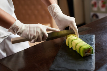 Closeup view of process of preparing rolling sushi. Chef is cutting roll on the black stone plate