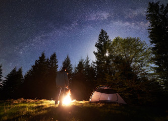Camping site in mountain valley at night. Silhouette of male hiker resting in front of tourist tent at burning bonfire under night starry sky with Milky way and full moon. Pine trees on background