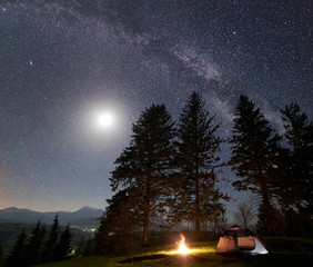 Night camping in mountains. Tourist tent by burning campfire under amazing beautiful dark blue starry sky, full moon and Milky way. High pine trees on background. Outdoor activity, tourism concept
