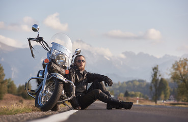 Handsome motorcyclist in black leather clothing sitting at modern powerful shiny motorcycle on grassy roadside on blurred copy space background of distant mountain peaks under bright sky.