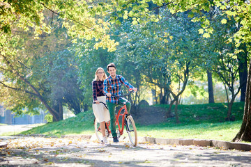 Young active smiling traveler couple, handsome bearded man and attractive blond woman cycling together tandem double bike along crackled path in lit by bright morning sun beautiful park under trees.