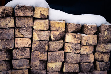 A Wall of Bricks With Snow on Top