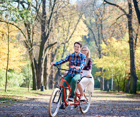 Young active couple, handsome bearded man and attractive blond long-haired woman cycling together tandem double bike by sunny alley with golden leaves on tall trees background