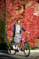 Young happy long-haired smiling blond woman in casual clothing and glasses cycling pink lady bicycle on bright warm sunny day on background of brick wall overgrown with beautiful red ivy leaves.