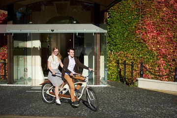 Young smiling tourist couple, handsome man and pretty long-haired blond woman cycling tandem bike on bright sunny day