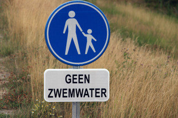"""sign with dutch text """"geen zwemwater"""" which means in english """"no swimming water"""" with above sign indicating pedestrian lane"""