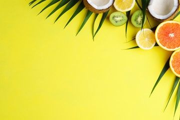 summer composition with exotic fruits and palm leaves on bright background. summertime vacation, cocktail, tropical beach. creative layout, banner or poster template with copy space for text design