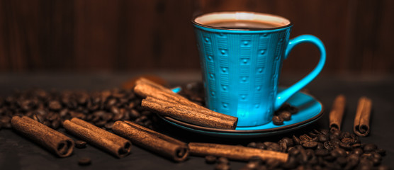 Cup of aromatic black coffee, coffee beans and cinnamon sticks on dark background. Still life. Panoramic banner.