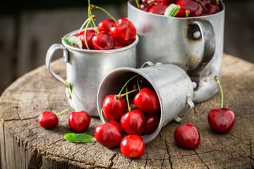 Ripe sweet cherries in the old metal mug