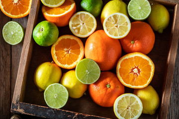 Tasty oranges, limes and lemons with on rustic table