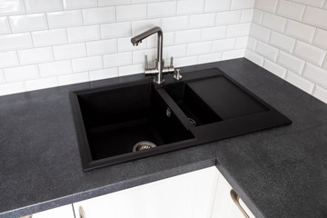 Black granite sink and a mixer mounted on a black countertop