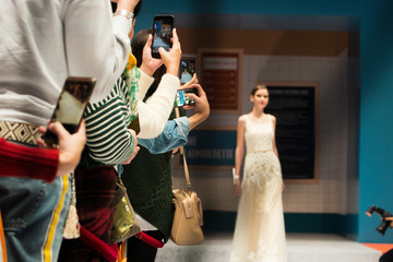 Fashion dress Model walk back on dark Runway Fashion Show catwalk along way finale, background stage ramp, copy space for text logo, audiences use smartphone mobile phone take photo bad manner way