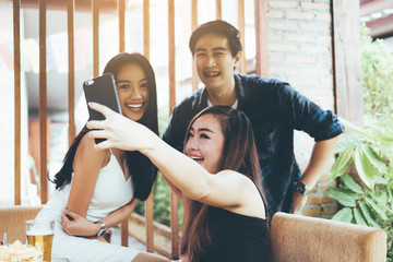 Teenage brides are having fun in the party and using mobile phone talking selfie photo.