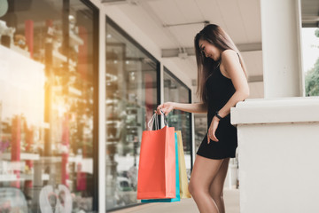 Asian teenage girls standing and holding shopping bags at shopping mall.
