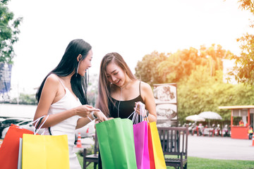Asian women standing at outlet mall and looking inside shopping bags paper.