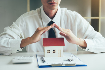 Hands covering or protective miniature model house on table with key and contract paper about insurance concept.