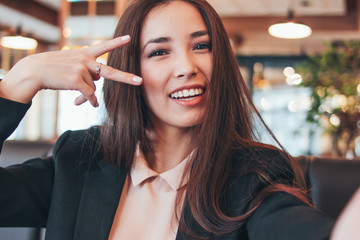 Beautiful charming brunette smiling asian girl taking selfie on frontal camera at cafe