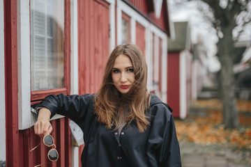 A girl with long hair stands on the background of a red wooden houses in Scandinavian style