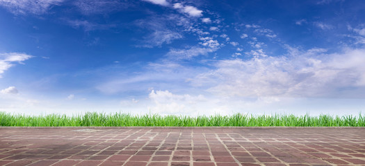 Empty concrete floor with blue sky and white clouds, with green grass field that grows in background as the bright nature of the sun.