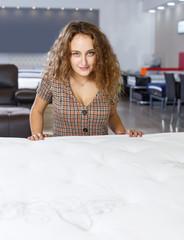 Woman choosing mattress in furnishings store