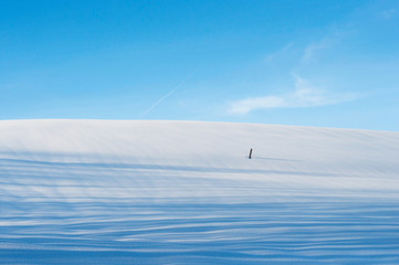 Winter landscape. Hill covered with snow and a blue sky over it
