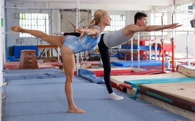 Foto auf Leinwand Gymnastik Mature woman and man gymnasts exercising gymnastic action at gym