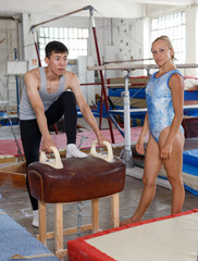 Man asian gymnast training at vaulting buck in gym, woman helping