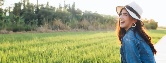 Young asian woman smiling in hat. Girl enjoying at beautiful nature with sunset. Travel Summer Holiday Vacation and Relaxation concept. Banner with copy space.