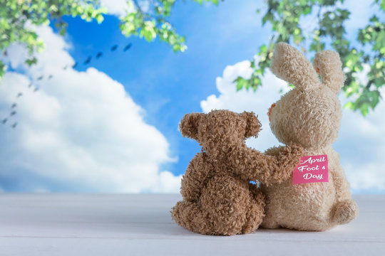 Two friends of the toy bears are sitting on the boards against the background of the summer sky on April Fool's Day with a sticker on the back, humor, a joke