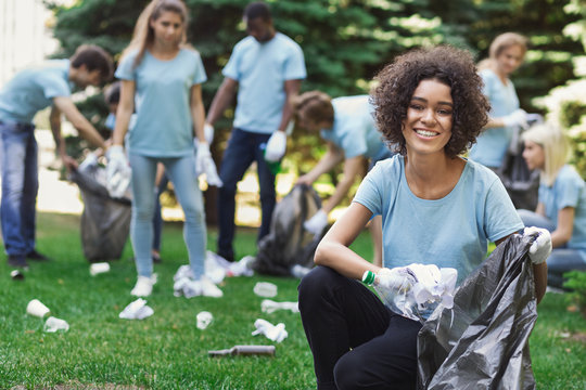Group of volunteers with garbage bags cleaning park