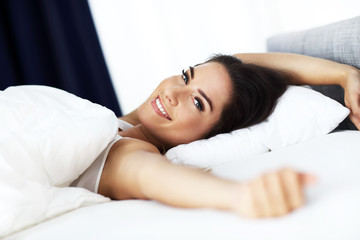 Young beautiful woman waking up in her bed fully rested