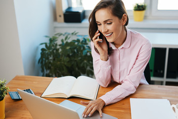Young woman talking on phone working on laptop in office