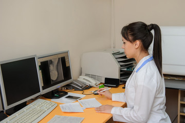 Young radiologist doctor edit and analyzes the digital  x ray on the computer