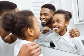 African-american girl brushing teeth together with dad