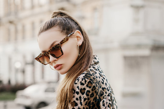 Outdoor close up fashion portrait of young beautiful fashionable woman wearing stylish animal, leopard print sunglasses, hoop earrings, blazer, walking in street of european city. Copy, empty space