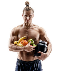 Resting time. Handsome muscular man holding fresh fruits and big jar of sports nutrition isolated on white background. Organic food and health concept
