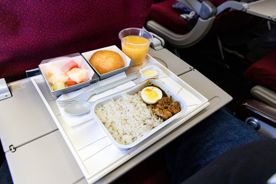 Basic inflight meal consisting rice, egg, beef curry, bread, juice.
