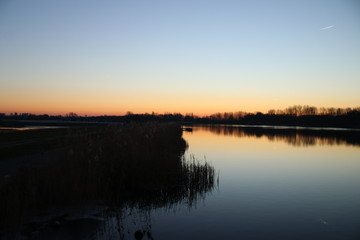 Sunset is reflecting over the water of the Rottemeren and river Rotte at Zevenhuizen close to Rotterdam in the Netherlands