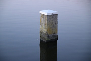 Mooring post reflecting in river Rotte at the Rottemeren in Zevenhuizen in the Netherlands