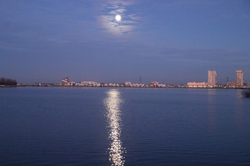 Full moon is rising above Nesselande beach reflecting on the Zevenhuizerplas as seen at Oud Verlaat just after sunset.