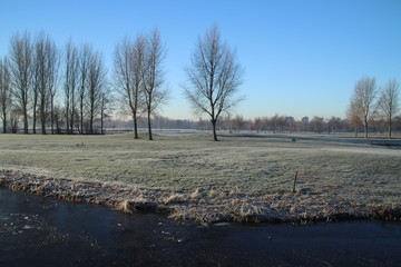 Frozen meadows and water with fog during colorful sunrise in Park Hitland at Nieuwerkerk aan den IJssel in the Netherlands