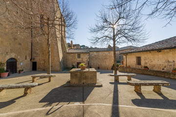 The sun filters through the branches of trees on Piazza Commenda in Monticchiello, Siena, Tuscany, Italy
