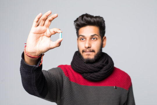 Concerned young arabic man in sweater, scarf holding daily pill isolated on grey background. Healthy lifestyle, ill sick disease treatment, cold season concept.