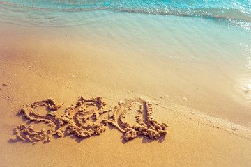Vacation on the sand beach concept. Sea words written into the sand on the beach at Rayong, Thailand.