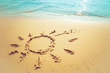 Vacation on the sand beach concept. The Sun symbol, sunshine drawing into the sand on the beach at Rayong, Thailand