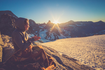 Girl sitting on a rock and covered with a blacket is watching Sunset From the top of the Mountain in a glacier area in the Alps with snow and blue sky