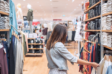 Young asian woman choosing clothes in clothing store at the mall, woman shopping lifestyle concept