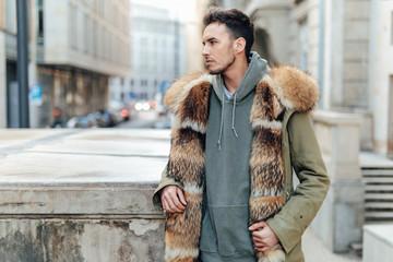 Fashionable man walk outdoors wear  fur jacket with street background - Image
