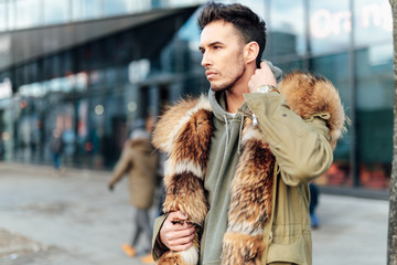 Fashionable man walk outdoors wear  fur jacket with street background - Image